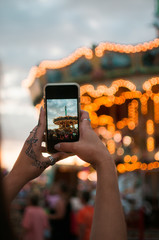 A young woman taking pictures on her phone of a carousel
