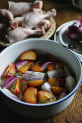 Plums red onions and thyme in a pot with olive oil.