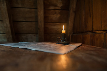 Candle light illuminates a newspaper on table