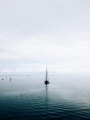 Sailboat Anchored In Still Ocean Waters