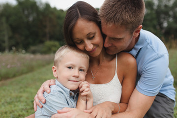 A family with young boy hugs together