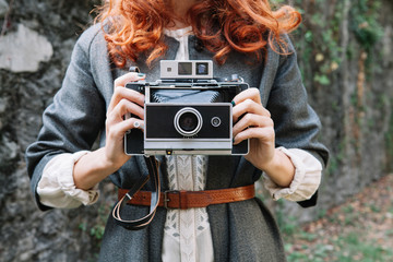 Woman with red hair and vintage camera