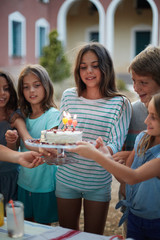 Young girl and friends carrying a cake for celebrating a birthday