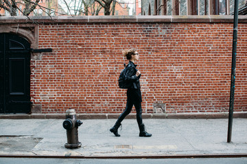 Young woman in black walking down the street