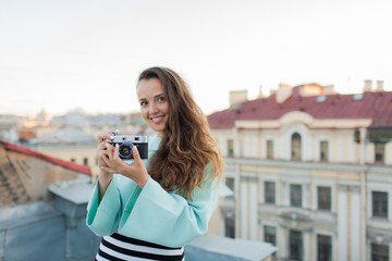 Fashion look, pretty cool young woman model with retro film camera. curly hair outdoors. Stylish girl photographer takes the old city from the roof at sunset.