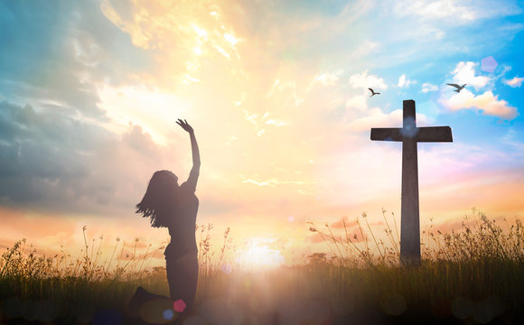 Happy thanksgiving day concept: Silhouette of beautiful woman kneeling and raised hands on the cross autumn sunrise background