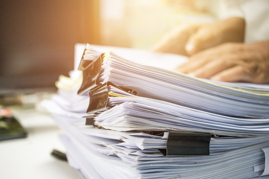 Businessman hands searching information in Stack of papers files on work in office, business report paper or piles of unfinished documents achieves with clips on offices Business concept