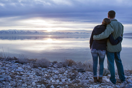 couple embraces as they look out over the sunset on the great salt lake