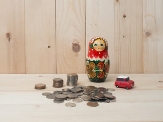 oney coins stack growing with green car on wood background. traveling growth investment and financial concept ideas.Russain doll and coins on table.