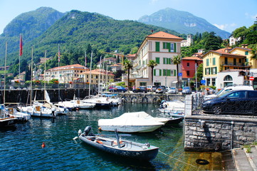 Lakeside view and a dock with boats of a small village on Lake Como in Italy