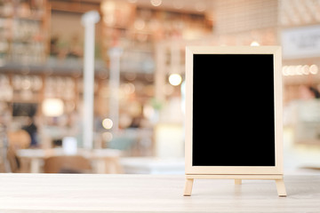 Blank chalkboard standing on wood table over blur restaurant with bokeh background, space for text, mock up, product display montage