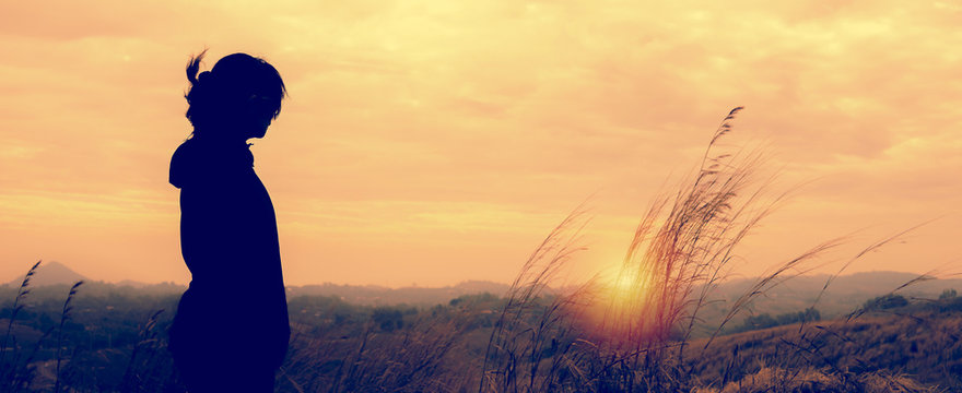 A woman standing alone in sunset scene.