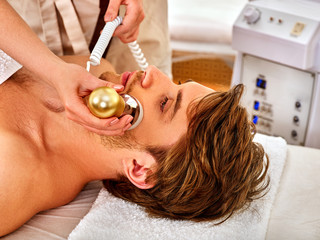 Skin resurfacing procedure facial procedure on ultrasound face machine. Male acne treatment. Man receiving electric lift massage at spa salon. Forced rest in the spa salon.