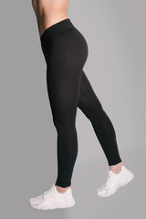 Woman in leggings and sneakers, low section. athletic ass