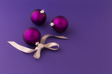 Beautiful purple christmas balls with satin effect and grey gift ribbon on purple background.