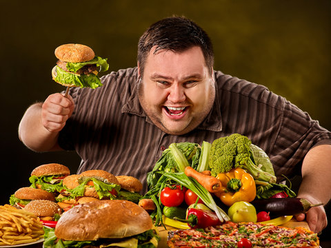 Diet fat man who makes choice between healthy and unhealthy food. Overweight male with hamburgers. Table with food in the foreground.