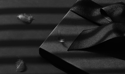 Black gift box on a dark contrasted background, decorated with a textured bow and feathers, creating a romantic atmosphere.