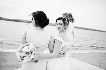 Stunning bride with pretty bridesmaids posing with bouquets on the lakeside. Black and white photo.