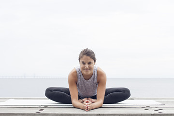 Woman sitting in yoga pose stretching her tights