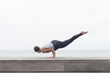 Woman doing yoga arm balance by the sea