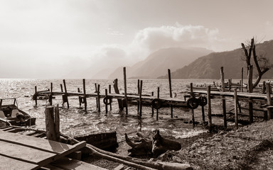 Rural landscape with old rickety wooden piers out into Lake Atitlan in Guatemala on the shore in Panajachel village with highlands in the background.