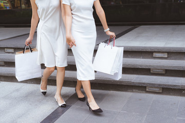 Friends go shopping. Two young women walk on shopping mall with bags