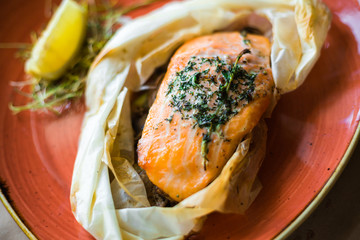 On a wooden board, on a red plate a salmon steak, in craft paper, lemon, rosemary, spices, two pepper mills, delicious fashionable food, high cuisine, beautiful serve, restaurant, dinner, lunch