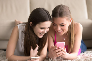 Portrait of pretty young woman lying on carpet and showing funny photos or videos on cellphone to her girlfriend. Sisters resting and chatting at home, using mobile app, sharing news, shopping online