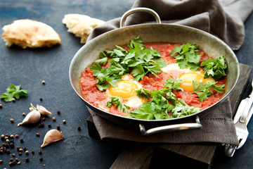 Shakshuka fried eggs with tomatoes, onions and spices in frying pan on a dark blue cracked background