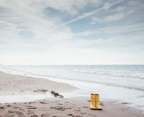Gelbe Gummistiefel am Strand