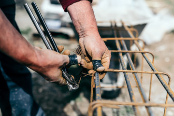 worker hands using steel wire and pincers to secure steel bars, preparing for concrete pouring on indutrial construction site.