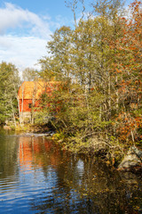 Mill at a forest lake in autumn