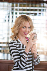 Beautiful girl with a microphone in a striped suit.