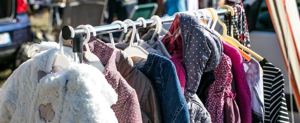 rack of second hand winter baby jackets at flea market