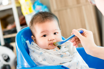 Portrait of adorable infant baby girl sitting on the chair and eating baby food