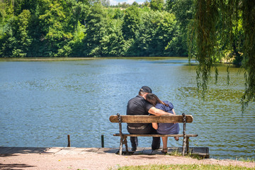 Couple in love on a bench near a lake