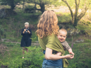 Mother with baby posing for grandmother in nature