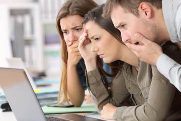 Worried employees reading bad news on line