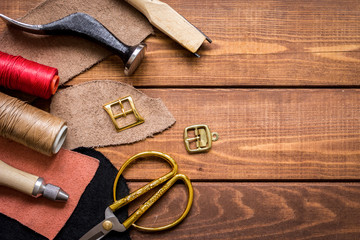 leather craft instruments on wooden background top view