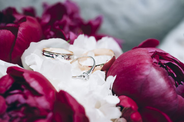 Two wedding rings made of yellow gold and one engagement ring of white gold with diamond placed on a peony bouquet