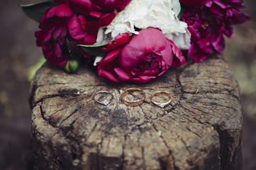Two wedding rings made of yellow gold and one engagement ring of white gold with diamond on a old wood stump with some pink and white peonies on the background