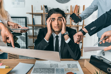 overworked businessman missing deadline due to work while colleagues pressing near by