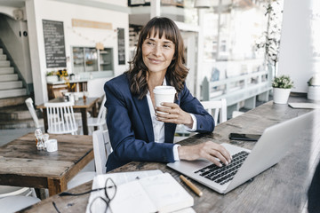Businesswoman sitting in cafe using laptop and drinking coffee