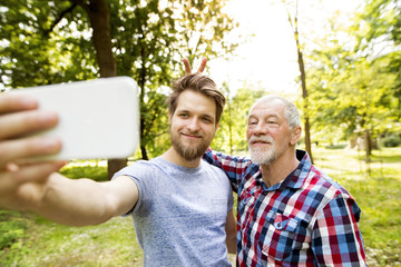 Portrait of senior father and his adult son taking selfie in a park