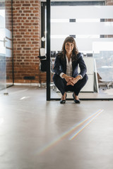 Successful businesswoman crouching in office