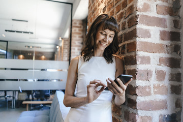 Businesswoman standing in office, holding smartphone