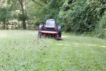 mowing grass zero turn mower cut and tall grass red machine
