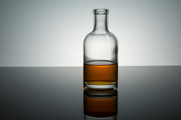 small clear bottle half full of burbon on reflective surface