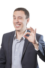 Businessman smiling and showing a gesture Ok, isolated on a white background