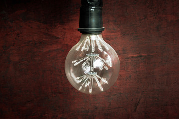 Decorative antique classic light bulb against dark red old rusty metal plate. Classic bulb over rust texture background.